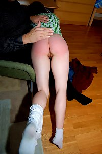 Gorgeous redhead girl is taken OTK for a sound spanking on her bared bottom