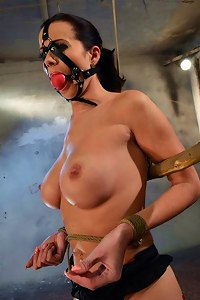 Master squeezes tits of a beautiful nude bondage babe dressed up in stockings and gagged with harness  Submissed