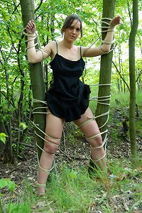 Bound girl between trees in the forest