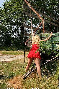 Blonde standing outdoor tied to rusty trailer