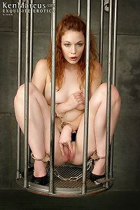 Submissive redhead centerfold Justine Joli gets caged and plays with her dildo in the dungeon