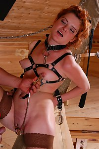 Redhead in belt bondage gets flogged, waxed and pussy clamped